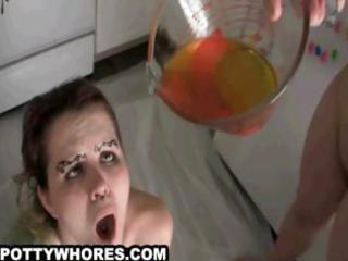 sexy goth chick fills a glass with pee and drinks