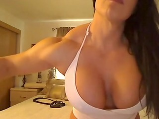 muscled woman wearing just a pink top shows her
